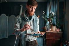 Artist paints colors on the palette, art studio Stock Image