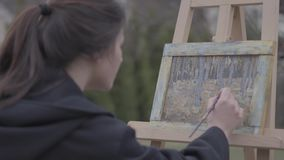 Pretty successful artist paints on the canvas in the backyard. Beautiful enthusiastic girl engaged in creativity. Art. The artist paints on the easel in the stock footage