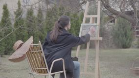 Skilled artist paints on the canvas in the backyard. Beautiful enthusiastic girl engaged in creativity. Inspiration. The artist paints on the easel in the stock footage
