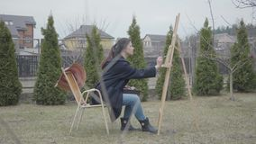 Skilled artist paints on the easel in the backyard. Beautiful enthusiastic girl engaged in creativity. Inspiration. The artist paints on the easel in the stock footage