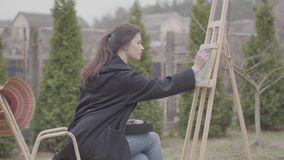 Skillful artist paints on the canvas in the backyard. Beautiful enthusiastic girl engaged in creativity. Inspiration. The artist paints on the easel in the stock video footage