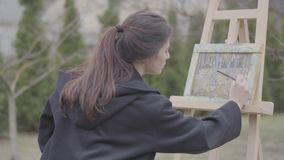 Successful artist paints on the canvas in the backyard. Beautiful enthusiastic girl engaged in creativity. Art academy. The artist paints on the easel in the stock video footage