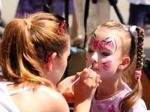 Artist paints on face of little girl. Artist paints butterfly on face of cute little girl royalty free stock photo