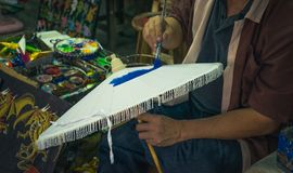 The artist paints a handmade umbrella in blue at a factory in Chiang Mai. Stock Photography