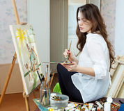 Artist paints the house on canvas. Yuong adult artist paints the house on canvas in studio stock photography