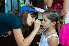 Artist paints mask on a girl's face on a children's holiday in the park in Volgograd Stock Images