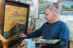 Artist paints oil painting with a brush and palette. Elderly artist paints a picture oil paints in his studio Stock Photos