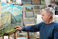 Artist paints oil painting with a brush and palette. Elderly artist paints a picture oil paints in his studio Royalty Free Stock Images