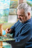 Artist paints oil painting with a brush and palette. Elderly artist paints a picture oil paints in his studio Stock Images