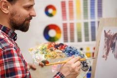 Artist paints with oil paints Stock Images