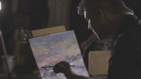 The artist paints a painting in the studio stock video