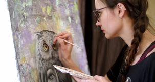Girl artist paints a picture Shaman. Artist paints picture on canvas with acrylic paints in her workshop. Artist paints picture on canvas with acrylic paints in stock video