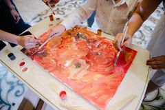 The artist paints a picture on canvas with paints royalty free stock image