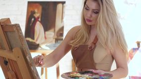 Artist paints picture on canvas mounted on easel, slow motion. Artist paints picture on canvas mounted on easel, in hands holds brush and palette, in background stock footage