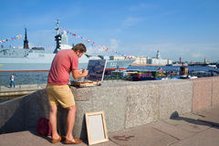 Artist paints a picture with a military ship on the Admiralty embankment in Saint Petersburg Stock Image