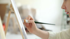 Artist paints a picture of oil paint brush in hand with palette closeup. 4k 20s. Artist paints a picture of oil paint brush in hand with palette closeup 4k 20s stock footage