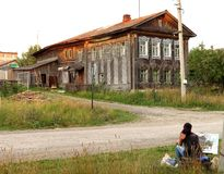 The artist paints a picture of the old village houses. Festival `Art-Chusovaya` ! The girl wants to portray the picture of a country house on the banks of the Stock Photography