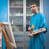 Artist paints picture in the studio. An artist paints a picture in the studio on canvas Royalty Free Stock Images