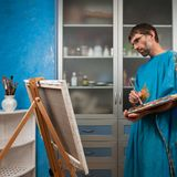 Artist paints picture in the studio. An artist paints a picture in the studio on canvas Royalty Free Stock Image