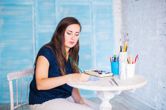Artist paints picture with watercolours. In her workshop Royalty Free Stock Image