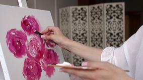 The artist paints pink flowers on canvas with brush, close-up. Art. Close-up girl paints peonies with brush on the canvas. The artist paints pink flowers on stock video footage