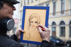 Artist paints a portrait. St. Petersburg, Malaya Konyushennaya, February 14, 2015. Artist paints a portrait. Street artist. Art. Drawing with pastel and pencil Stock Photos