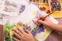 Artist paints watercolor. Paints on wooden table Royalty Free Stock Photography