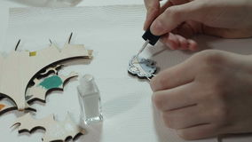 An artist paints on wooden craft.  stock video footage