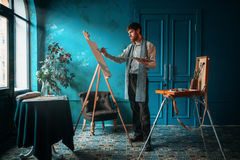 Artist with palette and brush paint on easel. Male artist with palette and brush in hand paint on easel in front of window. Oil paint, paintbrush drawing stock image
