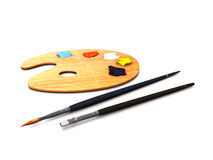 Artist palette and brushes. An artist palette with oilpaint and two brushes Stock Image