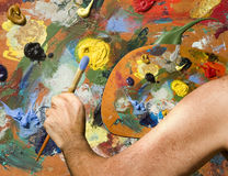 Artist with palette and canvas. Artist painting canvas precisely copying paints on palette stock image