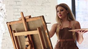 Artist with palette in hands creates her own brilliant masterpiece