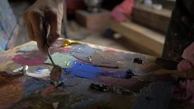 Artist palette knife mix color oil painting on palette is holding in his hand close up. In workshop. 4K stock footage