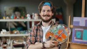Artist with Palette. Portrait of joyful artist with palette and paintbrush, feeling real satisfaction after completion of painting, wearing checked shirt and stock footage