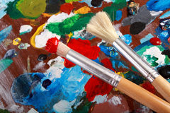 Artist palette and two paintbrushes. Classic artists palette with paintbrushes background Royalty Free Stock Image