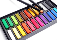 Artist pastels charcoal pencil. Playing a colorful xylophone! - A fun still life image of a box of 24 artists' pastel sticks and two black charcoal pencils at Stock Image