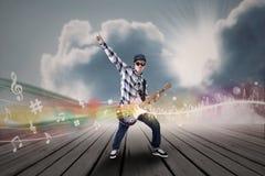 Artist perform guitar instrument under blue sky Stock Images
