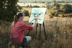 Artist on the plain air. Young girl-artist is painting with watercolor on the plein Air Stock Image