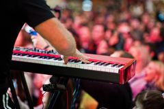 Artist play on audio piano on stage in a concert hall behing peoples.  royalty free stock image
