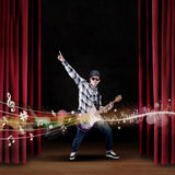 Artist play guitar on stage with musical notes. At the theater Stock Photo