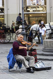 Artist playing a fiddle on Piazza della Repubblica in Florence Royalty Free Stock Image