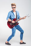 Artist playing guitar in studio background while posing Stock Photos