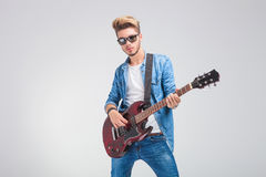 Artist playing guitar in studio background while wearing sunglas Stock Photos
