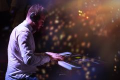 Artist playing on the keyboard synthesizer piano keys. Handsome young man with headphones playing on the keyboard synthesizer piano keys royalty free stock images
