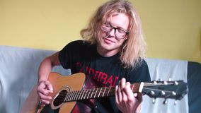 Artist plays acoustic guitar at rehearsal. The artist plays an acoustic guitar at a rehearsal. Holds a wooden guitar in his hands, plays it stock video