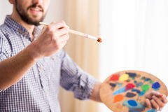 Artist. Portrait of a young male artist is holding a brush and mix color oil painting on palette Royalty Free Stock Image