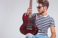 Artist pose in studio looking away with guitar in hand, on knee, Royalty Free Stock Photos