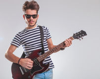 Artist posing while leaning and playing electric guitar Royalty Free Stock Photos