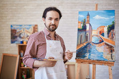 Artist Posing with Oil Paintings in Art Studio royalty free stock photo