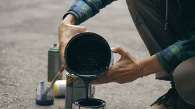 Artist pouring a black paint from can to another can. Close up shot of Artist pouring a black paint from can to another can on the ground stock video